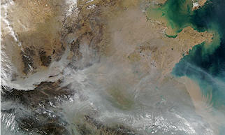 Sediments discharge into the Bo Hai Bay and western Yellow Sea colouring the surface waters caramel in this satellite view of China. Light brown hues show bare land, darker browns areas of vegetation. Photograph: Modis/Nasa