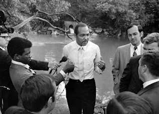 Cleveland Mayor Carl Stokes in front of the Cuyahoga River in 1969